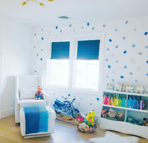 A baby nursery with blue polka-dot wallpaper and ombre blue window shades.