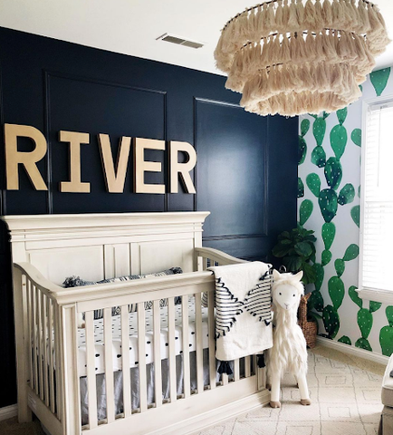A nursery with a dark blue painted accent wall and the word RIVER printed in gold behind the crib. The adjacent wall has green cactus-print wallpaper.