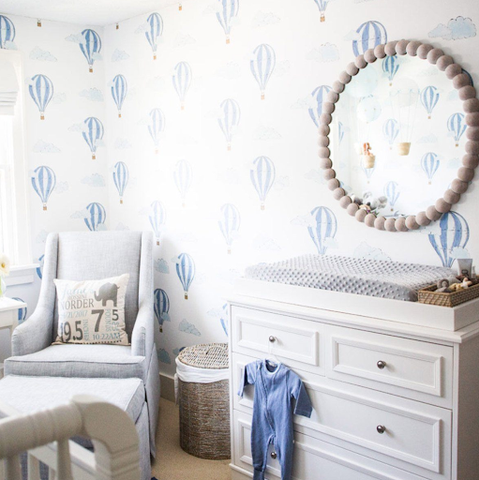 The corner of a nursery with white-and-blue hot-air-balloon-printed wallpaper.