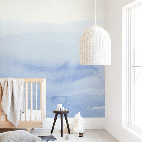 A blue baby nursery with a light blue water-color mural on the wall behind the crib.