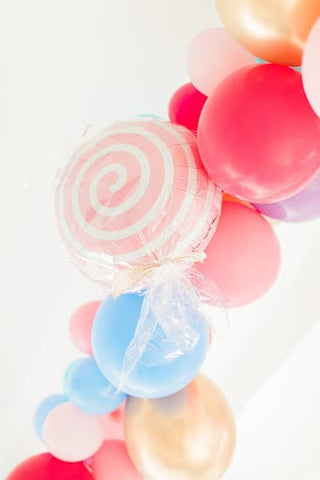 Candy colored balloons, plus one that looks like a striped lollypop for a fall baby shower