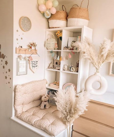 Neutral toddler nook with a cozy reading bench and bookshelves.