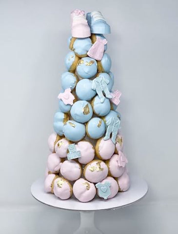Tower of pink and blue frosted cream puffs.