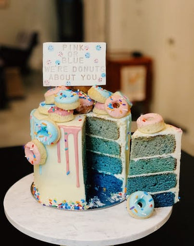 Gender reveal cake topped with donuts.