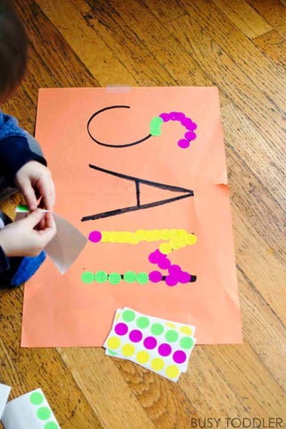 Toddler uses dot stickers to trace the name SAM on a piece of paper.