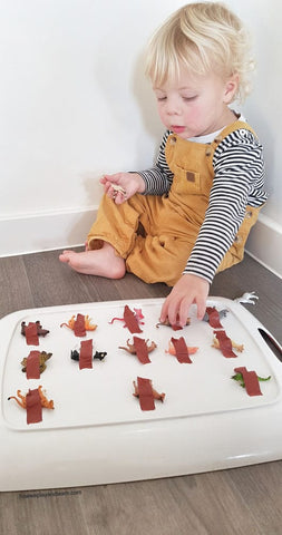 """A toddler tries to """"free"""" toy animals that have been taped down onto a tray."""