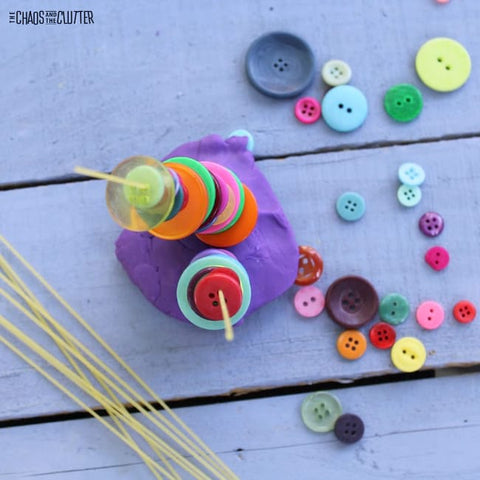 Buttons threaded and stacked on a dry spaghetti noodle that's held upright by playdough.
