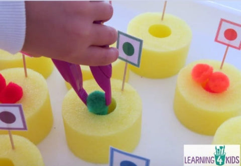 A toddler uses plastic tongs to put pom-poms into the donut-shaped pieces of a cut-up pool noodle.