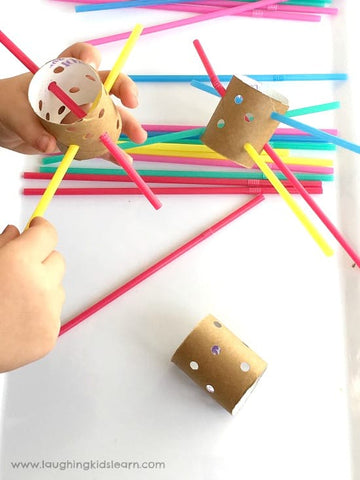 A toddler does a fine-motor threading activity with pipe cleaners and toilet paper rolls.