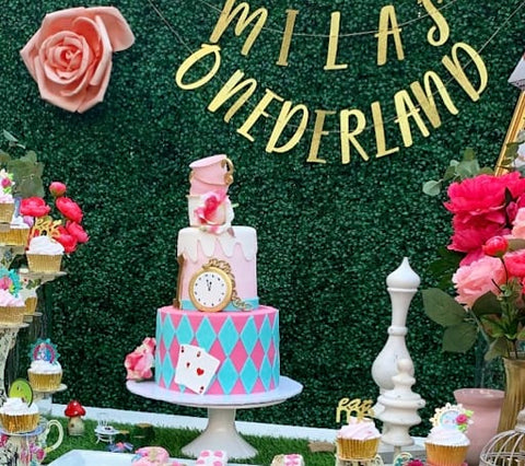 "Alice in Wonderland-themed first birthday cake on a table with a banner in the background reading ""Mila's Onderland"""