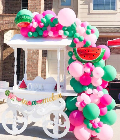 "Food cart draped with a pink and green balloon arch and a banner that reads ""one in a melon."""