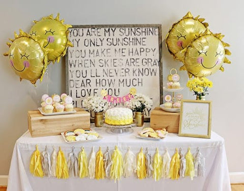 First birthday party table displaying sun-shaped mylar balloons, a yellow cake, and sun, cloud, and rainbow cookies.