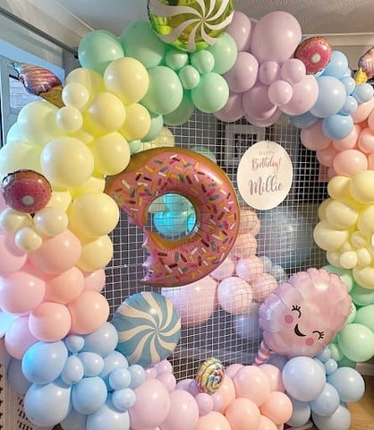 Pastel-colored first birthday balloon display featuring peppermint and donut-shaped mylar balloons.