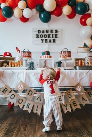 The back of a toddler boy wearing a baseball uniform standing in front of a baseball-themed party table.