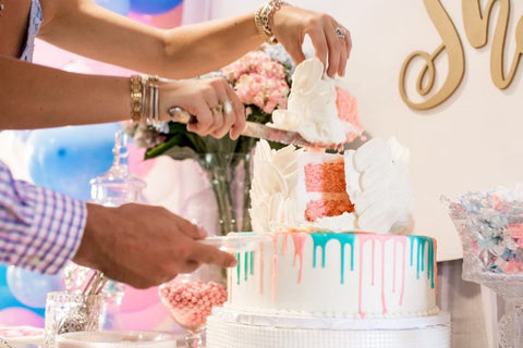 White gender reveal cake topped with pink and blue frosting that appears to drip down the cake.
