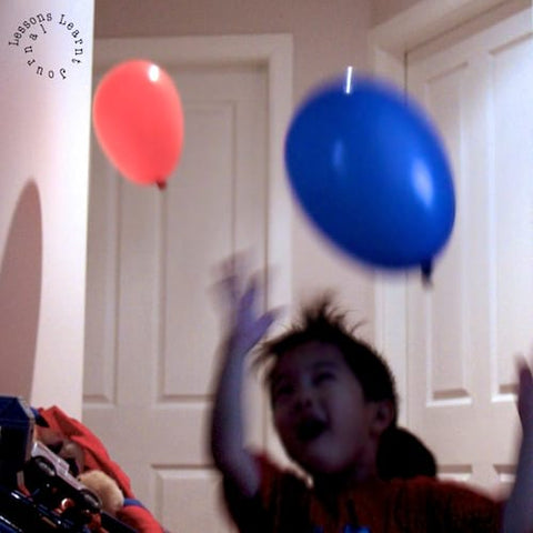 A toddler bats two balloons around his house.