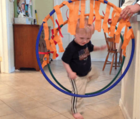 Toddler climbing through hula hoops decorated with orange streamers.