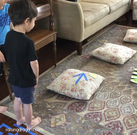 Toddler gets ready to complete an indoor obstacle course made from pillows