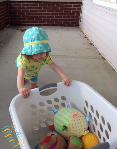 Toddler pushes laundry basket filled with toys.