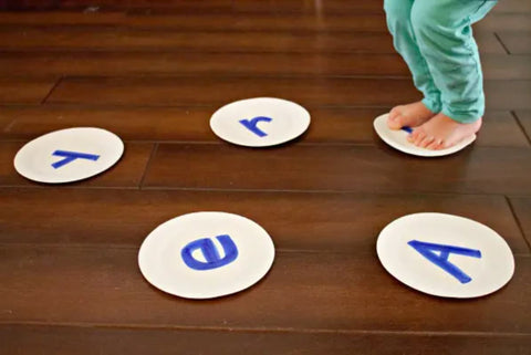 Toddler hops onto paper plates decorated with different letters.