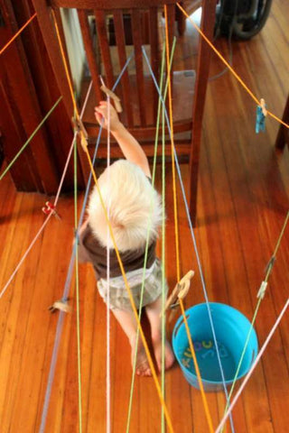 Toddler tries to get through maze made with string.