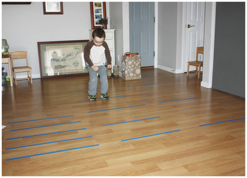 Toddler in living room jumping over tape lines on the floor.
