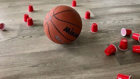 A basketball on the floor near knocked-over plastic cups after a homemade game of bowling.