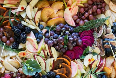 A spread of purple grapes, sliced red apples, figs, blackberries, and more for a fall baby shower