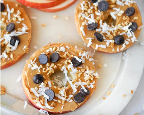 Apple rings topped with peanut butter, shredded coconut, and chocolate chips