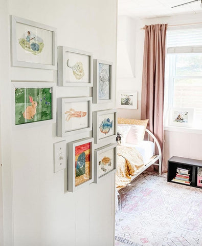 Gallery wall with framed pieces of child's artwork
