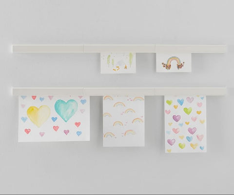 Kids art displayed on the wall with magnetic strips