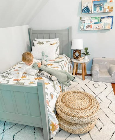Toddler room with a mint color scheme and dinosaur bedding.