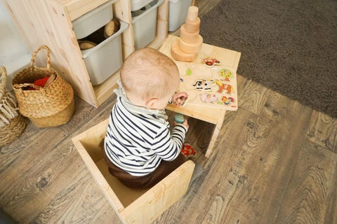 A baby plays at a child-sized desk in a Montessori nursery
