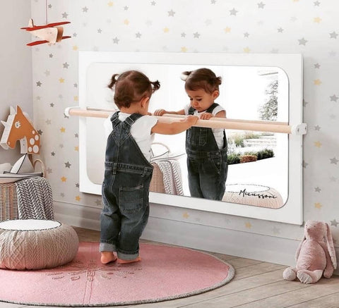 Toddler stands at child-size barre and looks in the mirror in a Montessori-style nursery