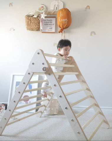 Baby climbs a Pikler triangle structure in a Montessori-style nursery