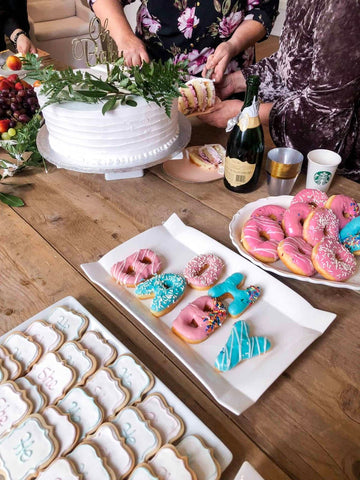 White gender reveal cake displayed on table with pink and blue donuts and cookies.