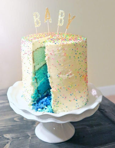 White frosted gender reveal cake with ombre blue sponge inside.