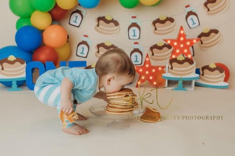 Baby eating stack of pancakes for birthday.