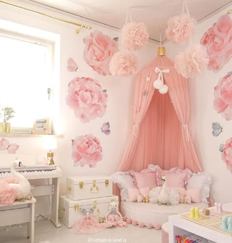Pink toddler bedroom with pink bed canopy and floral wallpaper.