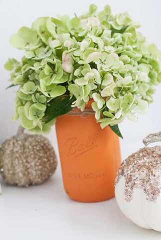 Pale green flowers in a terracotta mason jar and glittered pumpkins for a fall baby shower