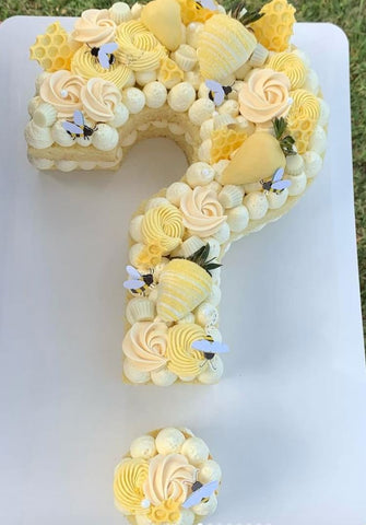 Question-mark-shaped bee-themed gender reveal cake.