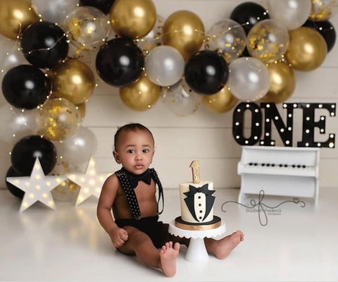 Baby in tuxedo outfit sitting in front of tuxedo-theme smash cake.
