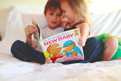 Sibling pregnancy announcement - big siblings reading a book