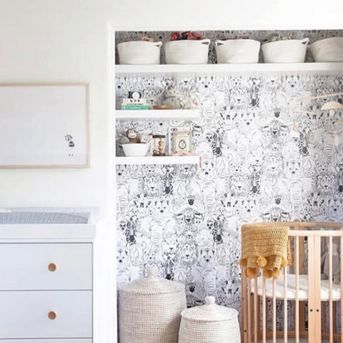 Closet that has been transformed into a nursery nook with floating shelves and a mini crib.