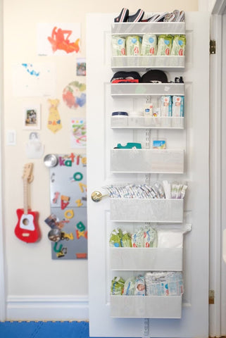 Hanging shelves filled with nursery essentials on the back of a door