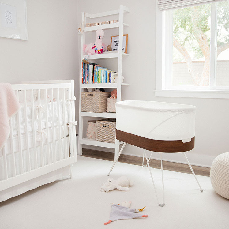 baby nursery with SNOO bassinet, white crib and white bookshelf