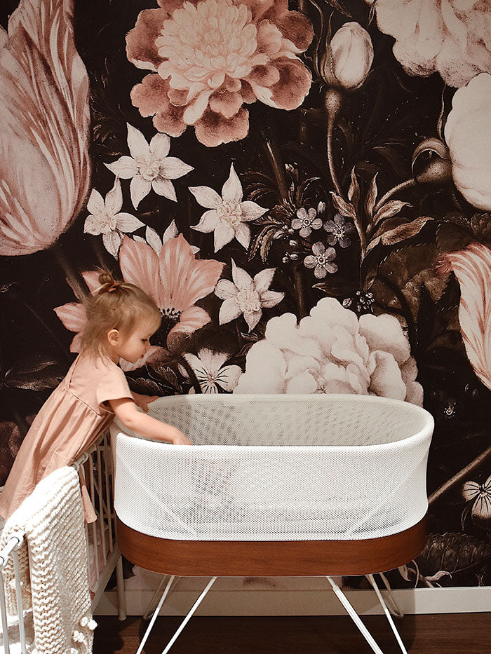 big sister visiting baby sister's nursery with flower wallpaper and SNOO bassinet