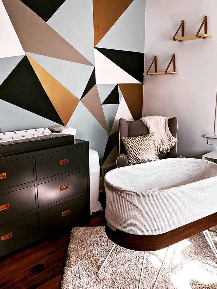 baby nursery with geometric pattern wallpaper and SNOO bassinet