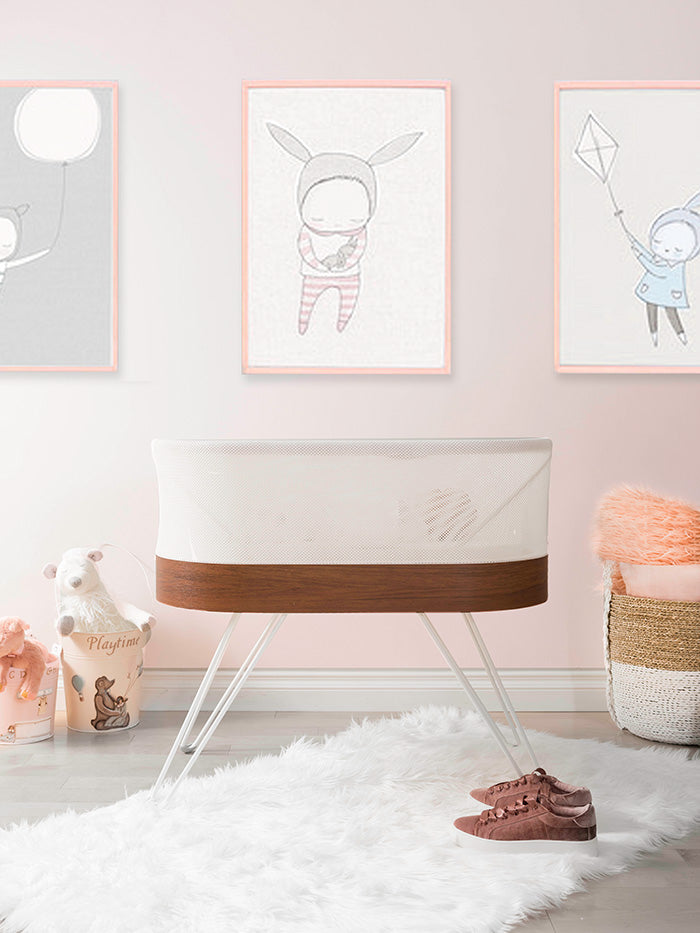 baby nursery with SNOO bassinet and pink wall