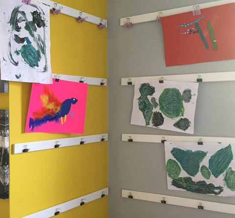Kids' artwork displayed on magnetic strips with clips.